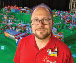 Matt Besterman with a tabletop model of the LEGOLAND New York theme park under construction.